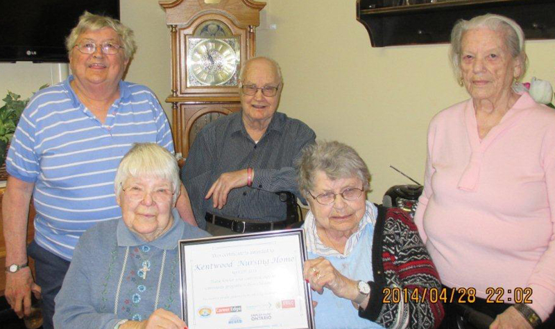 Kentwood Park residents pose for a photo with a community-service award the home recently received.