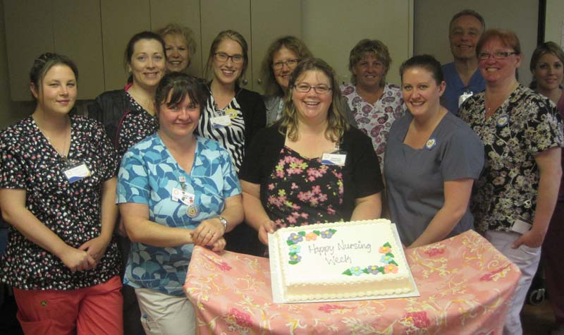 "The Riverview Manor team poses with a cake with the inscription ""Happy Nursing Week"" at a May 16 celebration of front-line staff."
