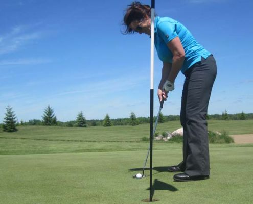 Sandra Clark of the DATA Group of Companies readies for a putt during OMNI's June 6 golf tournament.