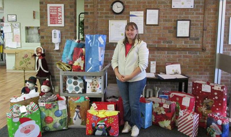 A member of the Christmas Elves stands next to the gifts the community group brought to Willows Estate last week. The group has bought about 180 presents for long-term care home residents without families this holiday season.