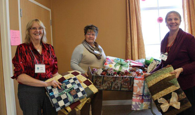 Springdale Country Manor LEC Sonia Murney (centre) is seen here with representatives from the Millbrook Needlers Quilt Guild. The guild donated Christmas gift bags to each of the home's 68 residents this year.