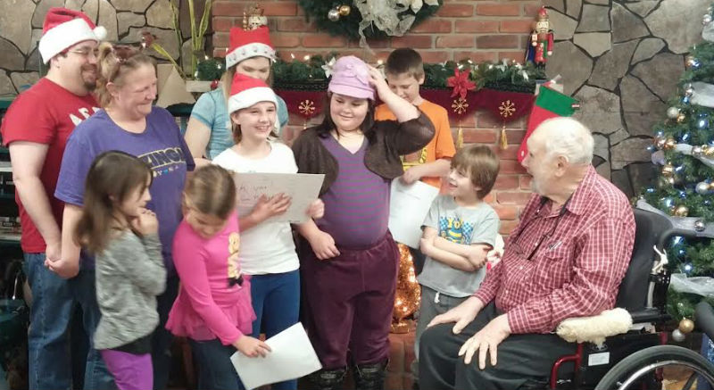 Halley Marsh (centre, white T-shirt) holds a thank-you card presented by Burnbrae Gardens residents' council president Frank Trombley on behalf of the home's 43 residents. Halley is making sure all residents at the Campbellford home get a present to open Christmas Day.