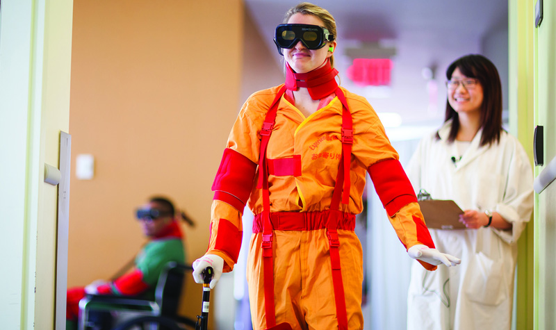 A student from the Working with Seniors program at Toronto's Michener Institute for Applied Health Sciences is seen here wearing a suit that simulates the mobility and vision challenges many seniors face.