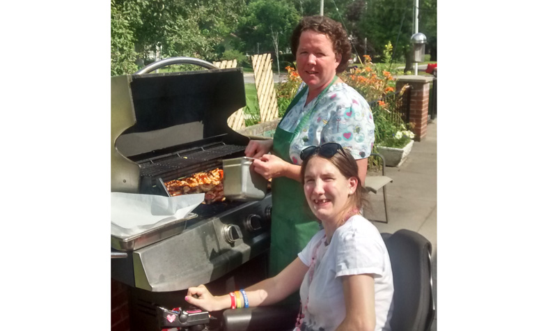 Maplewood cook Tracy Morewood and resident Corina Dempsey are seen during one of the home's many barbecues this summer.