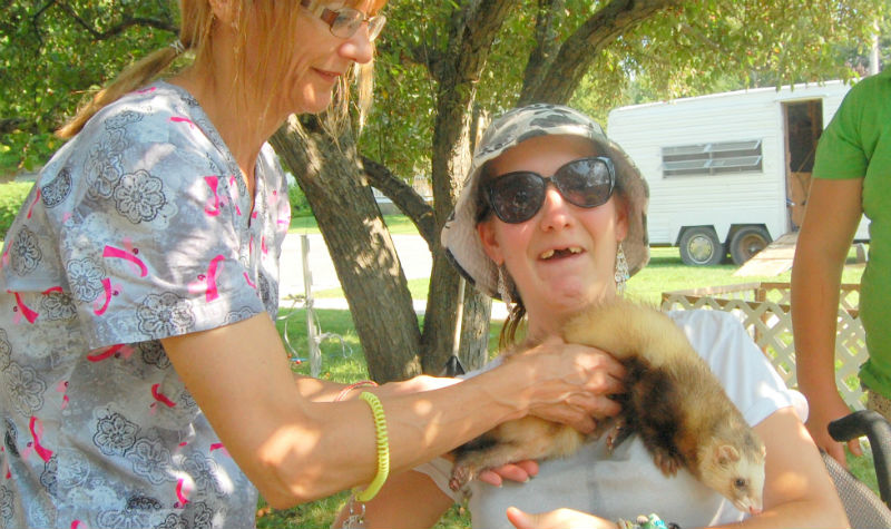 Maplewood resident Corina Dempsey, right, visits with a ferret as the Brighton long-term care home hosts a petting zoo.