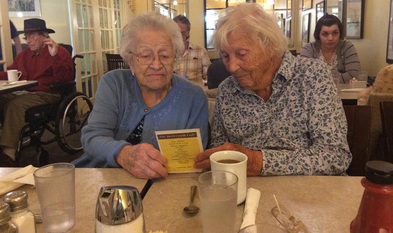 Streamway Villa residents (left to right) Mabel Goode and Betty Grinnell peruse the menu at Cobourg's Buttermilk Café during a recent outing.