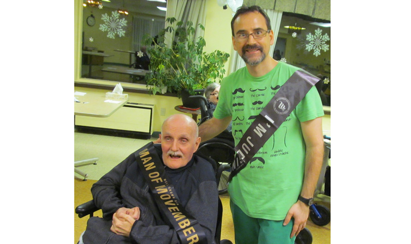 "Riverview Manor life enrichment aide Adam Wicklum (right) poses with resident Fred Maybee during the home's Nov. 30 party to mark the end of Movember. Twenty men from the home – 15 residents and five staff members – grew moustaches throughout November to raise money for men's health programs. Maybee was awarded the title of ""Man of Movember"" for his moustache."