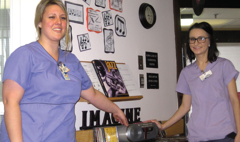 """Riverview Manor BSO team members Susanna Kelusky (left) and Logan Burrows (right) are seen here in one of the Peterborough long-term care home's two """"music corners."""" The areas have CD players with soft music playing throughout each day to help calm residents affected by agitation."""