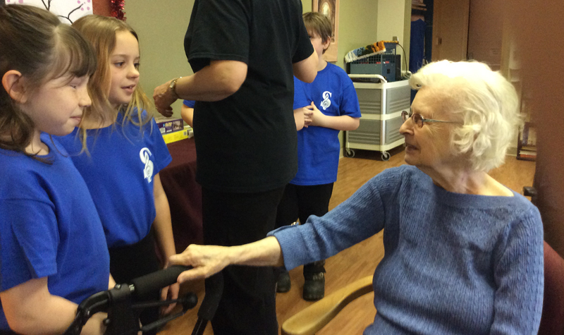 Village Green resident June Walters is seen here chatting with students from Southview Public School's choir on Feb. 11.