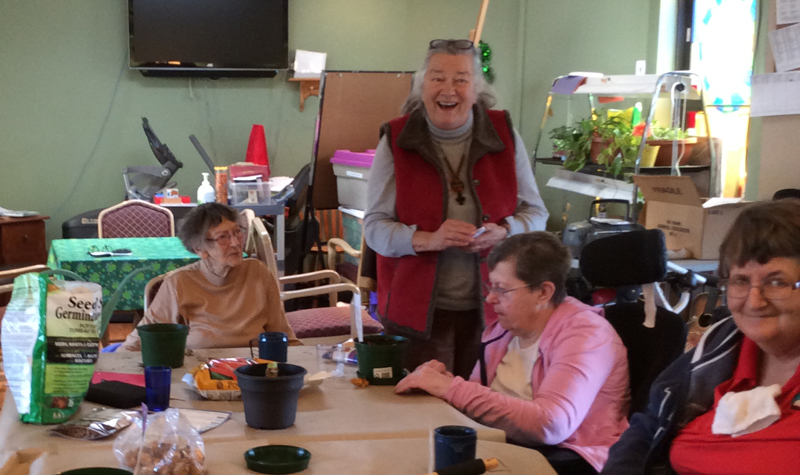 Rosebridge Manor volunteer Gillian Organ, seen standing, is helping residents plant flowers that will soon be placed in the home's gardens.