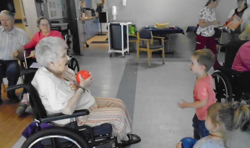 Maplewood resident Nancy Hanks is seen here playing catch with two of the children attending the Brighton long-term care home's June 11 fun fair.