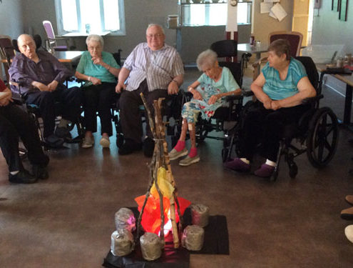 """West Lake Terrace residents are seen here gathering around the """"campfire"""" during an Aug. 17 program at the home."""