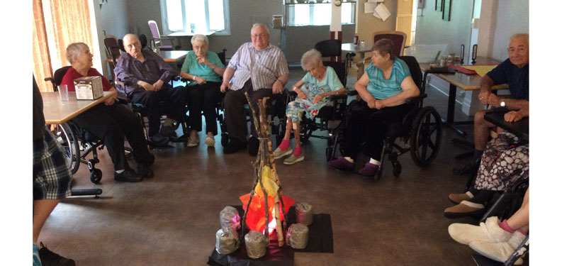 "West Lake Terrace residents are seen here gathering around the ""campfire"" during an Aug. 17 program at the home."