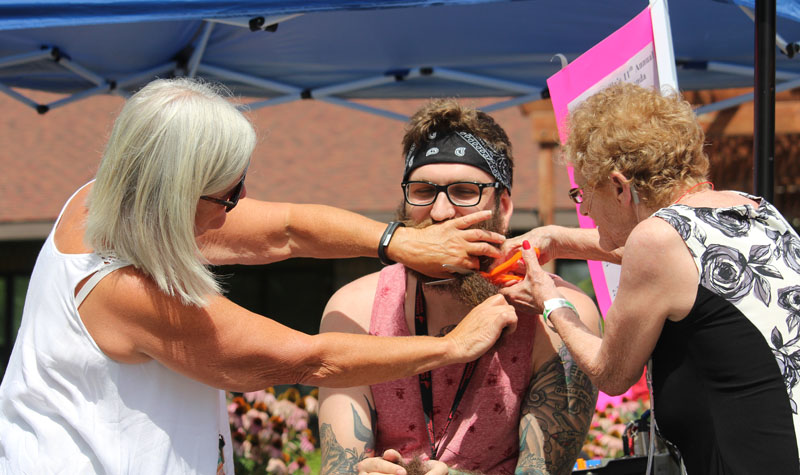 Resident Bernedette Lefleche joins in removing RPN Jake Hulse's beard as part of a fundraiser at the Woodland Villa Fair on Aug. 17