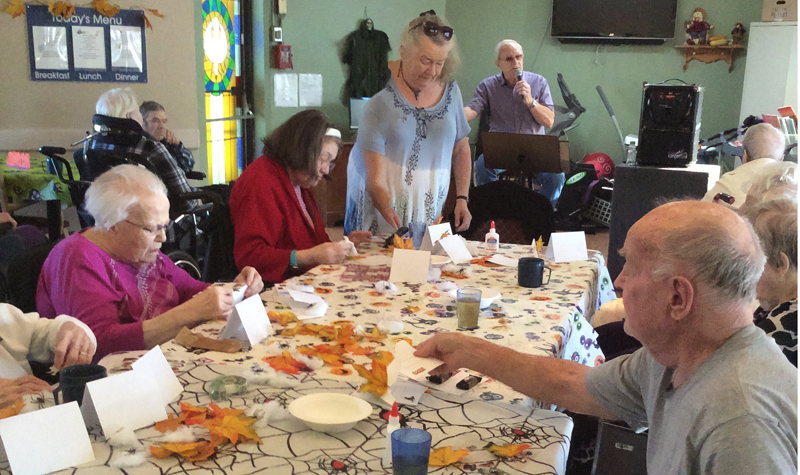 Rosebridge Manor volunteer Gillian Organ is seen here working with residents on creating place cards for the home's Halloween party.
