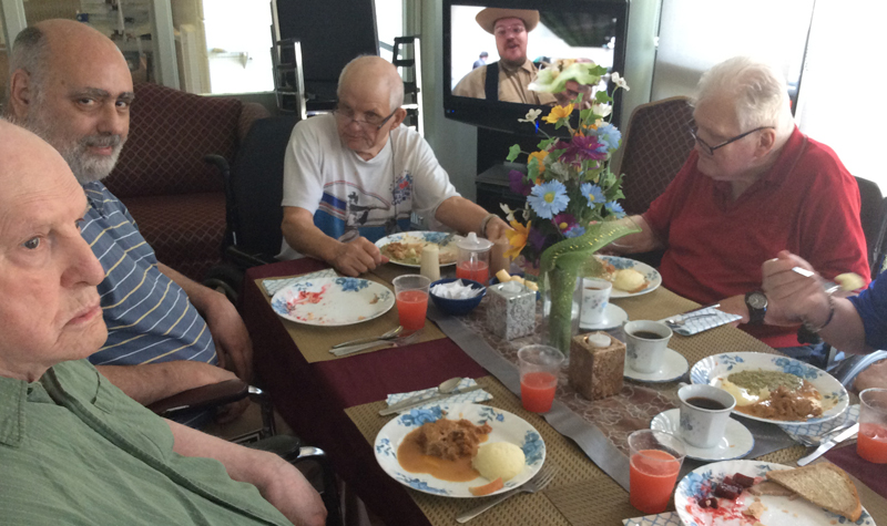 Pictured above, a group of men living at Rosebridge Manor are seen enjoying one of the home's Thursday night suppers. Each week for the past 15 years, Rosebridge has hosted small-group dinners. Meals are served on fine china and include a special dessert.