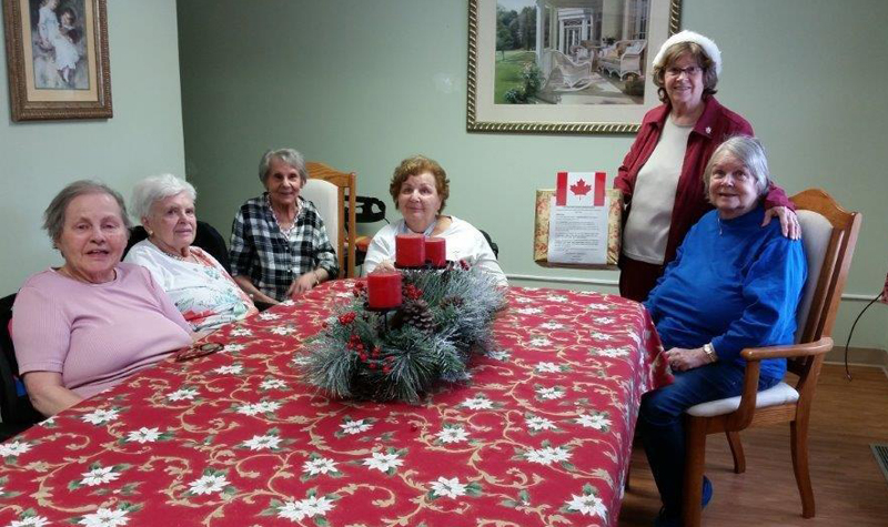 Willows Estate volunteer Dianne Harrison, pictured here standing, poses for a photo with some of the Aurora long-term care home's residents who helped send signed Christmas cards to Canadian troops stationed overseas. Dianne has collected about 3,500 Christmas cards from the community this year.
