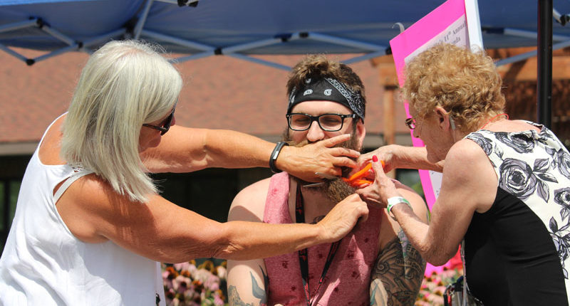 Resident Bernedette Lefleche joins in removing RPN Jake Hulse's beard as part of a fundraiser at the Woodland Villa Fair on Aug. 17.